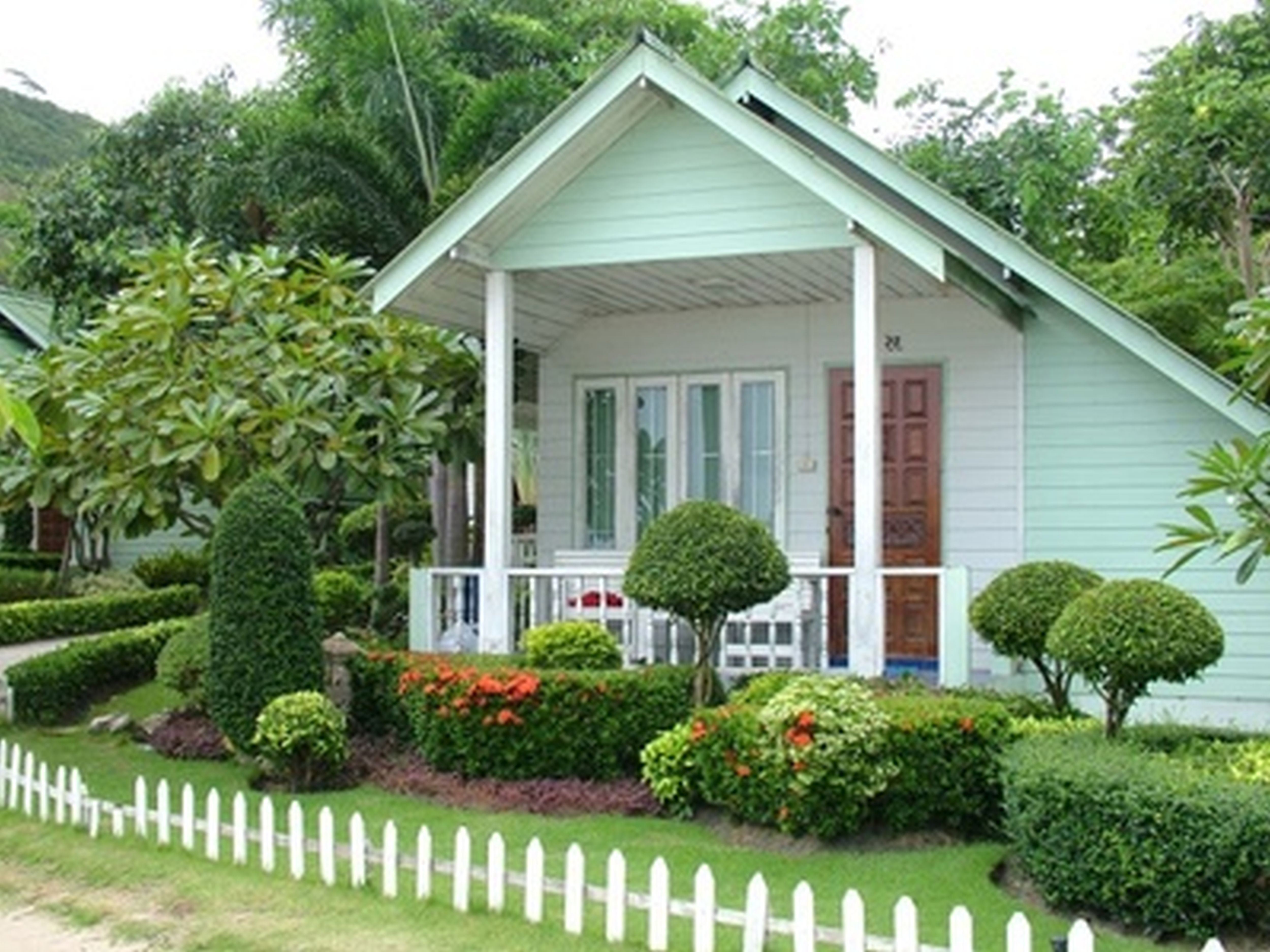 Add Low White Fence in Minimalist Front Yard Landscaping with Orange Flowers and Green Plants