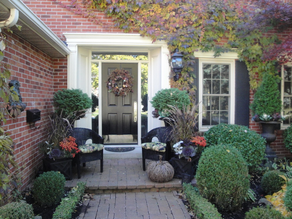 Add Natural Wreath on Dark Door for Small House Entry Space using Fall Decorating Ideas with Black Wicker Chairs