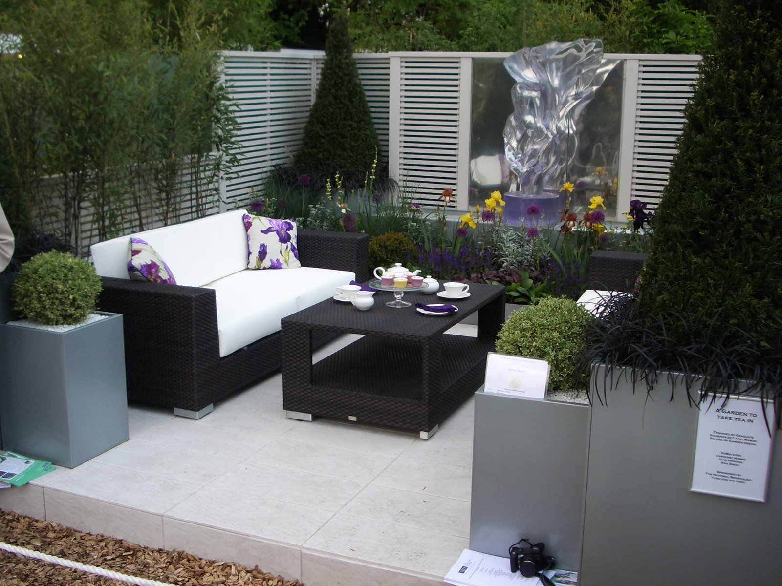 adding loveseat to complete seating unit of small patio with beautiful plants surrounding - Outdoor Small Patio Ideas