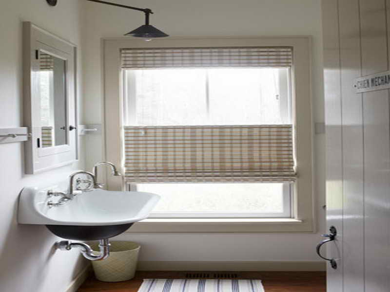 Ample Window in Small White Bathroom Treated with Double Blinds with Unique Pattern