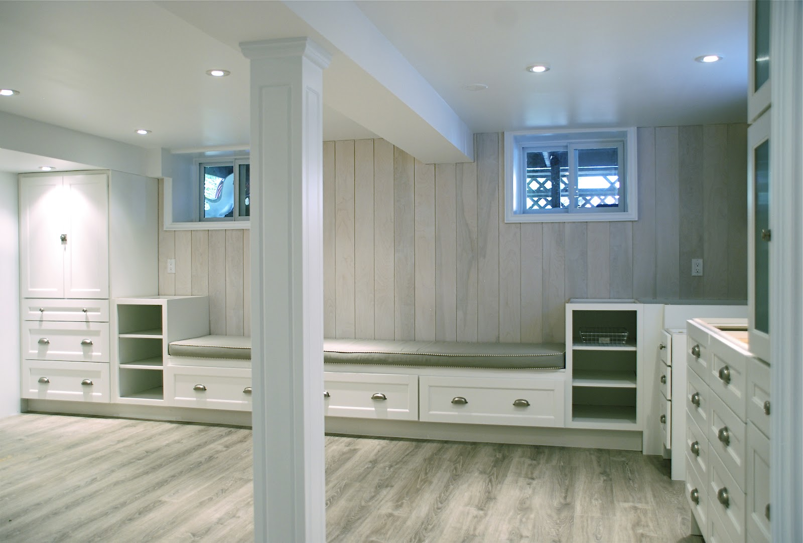 Appealing Wooden Flooring for Basement with Built in Cabinets and Seating