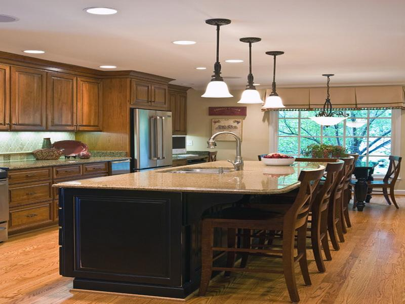 Bright Ceiling Lamps above Classic Kitchen Island with Wooden Seating and Glossy Sink near Wooden Cabinets