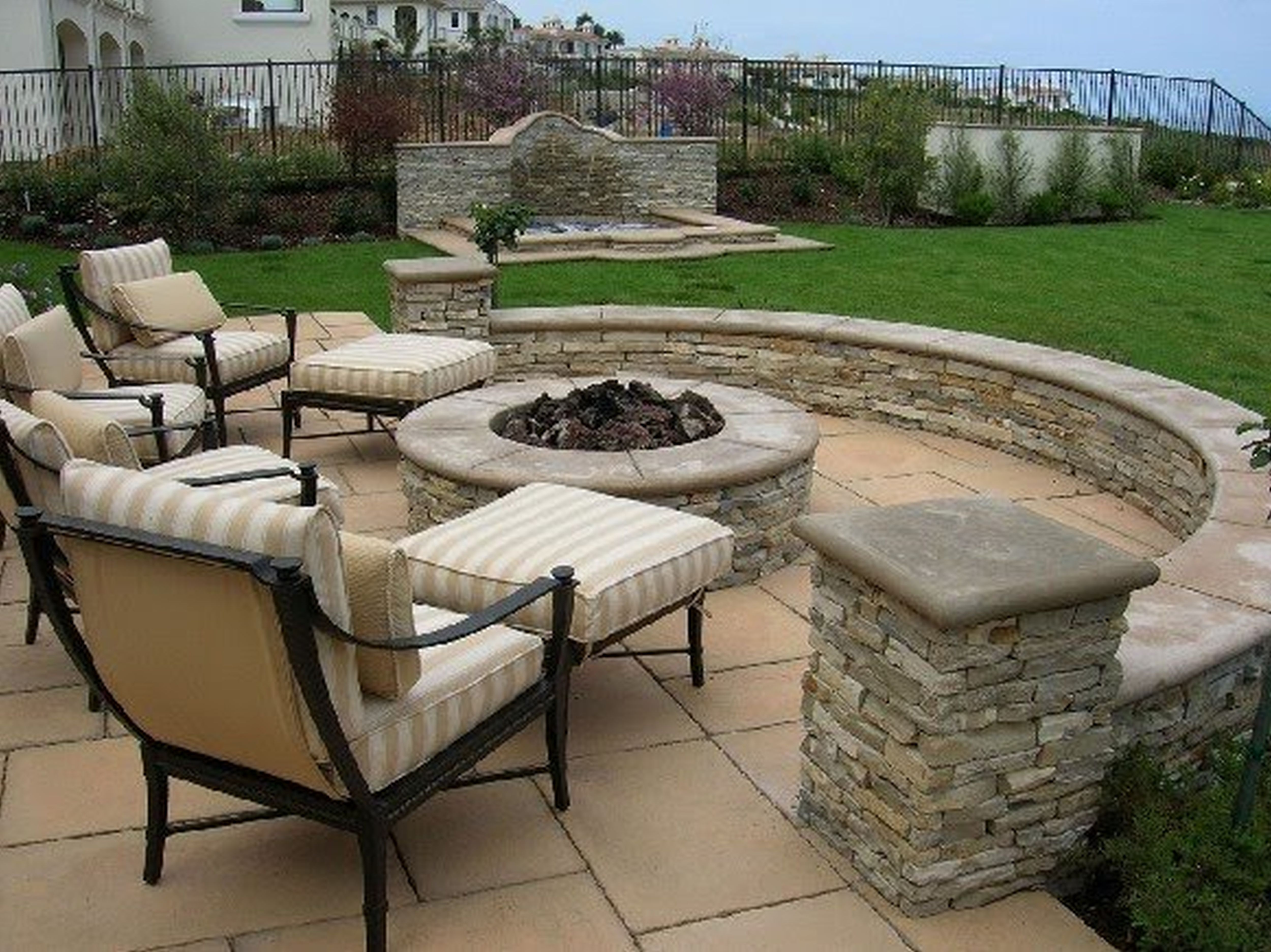 Classic Style Arch Patio with Rounded Fireplace and Four Chairs with Ottomans