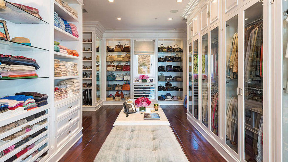 Colorful Clothes inside White Shelves and Drawers inside Spacious Walk In Closet with Tufted Bench