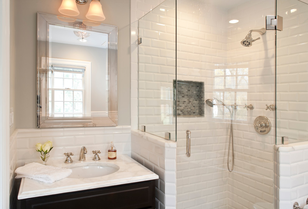 Complete Closed Glass Shower Area with Clean White Subway Tile Wall beside Dark Vanity and White Sink