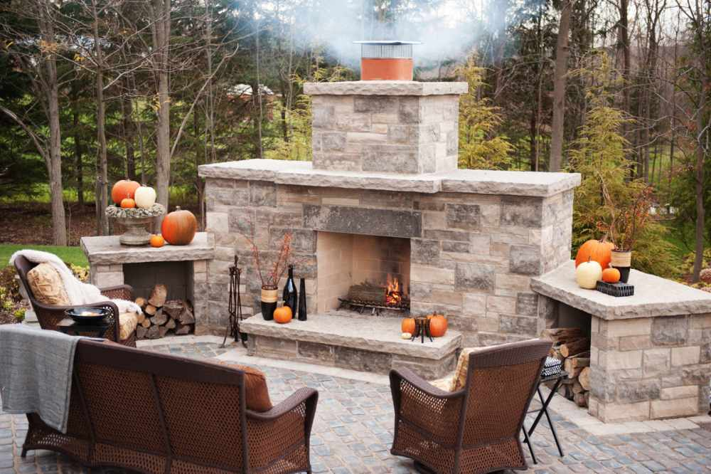 Cozy Outdoor Living Space With Traditional Seating Units And Stone Outdoor Fireplace