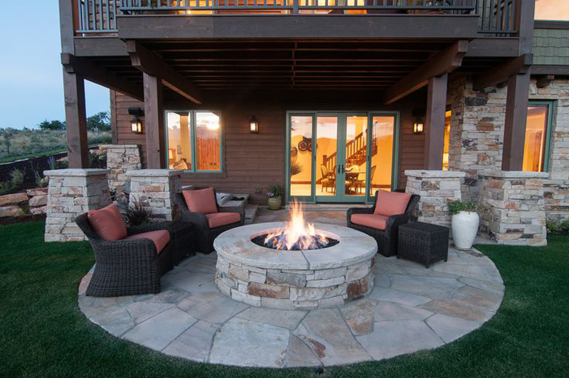 Cozy Outdoor Patio with Rounded Stone Floor with Fire Pit Surrounded with Armchairs