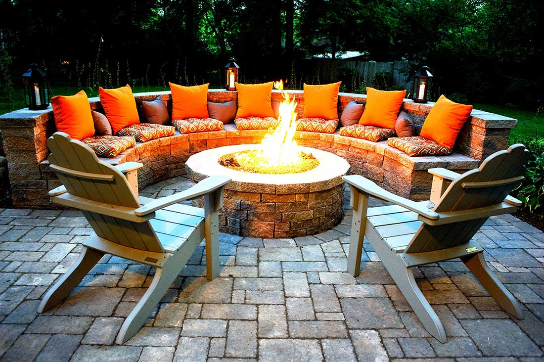 DIY Rounded Fire Pit Idea Surrounded by Built in Stone Seating Unit and Wooden Armchairs