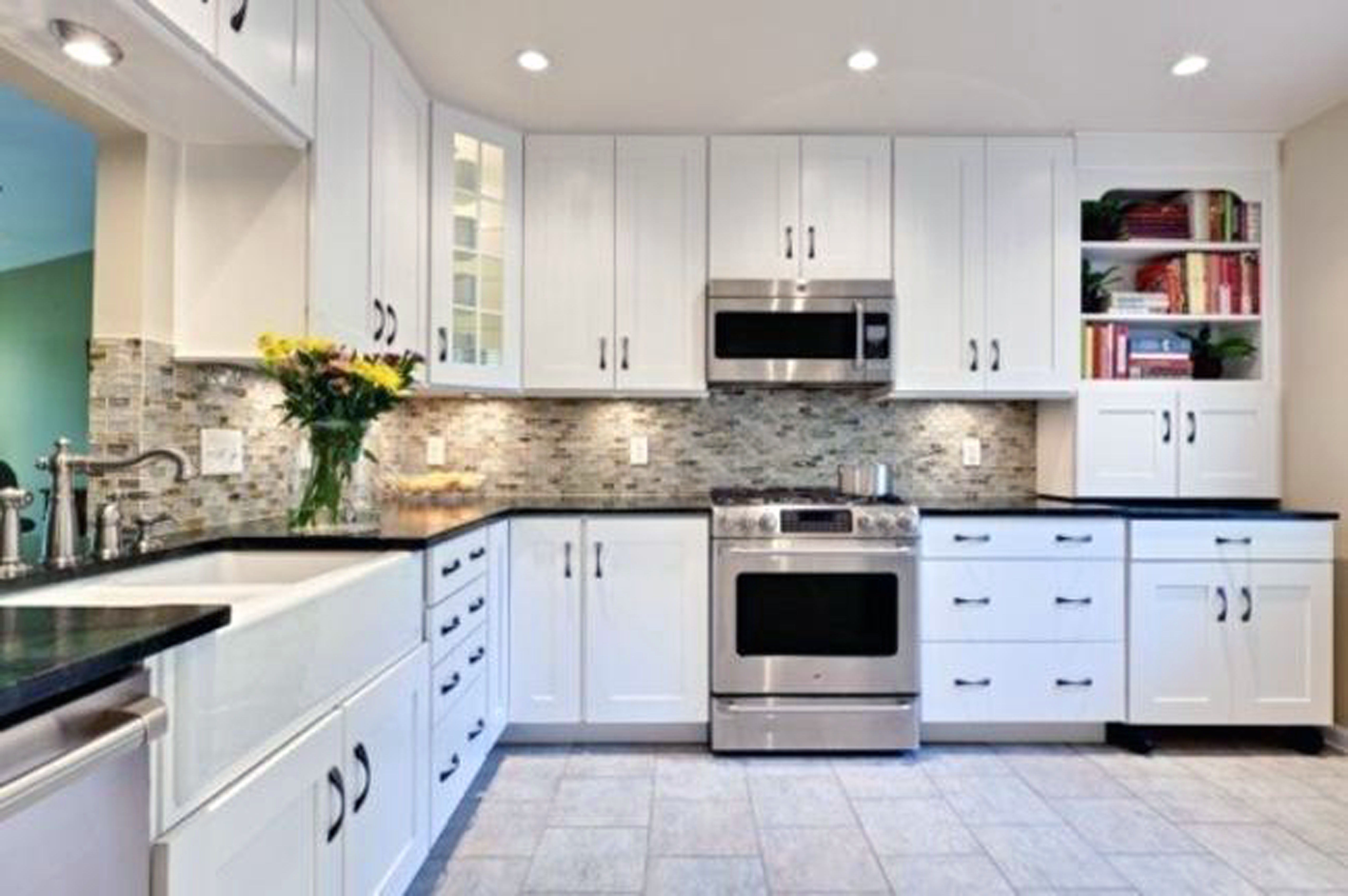 Illuminating Kitchen using Bright Under Cabinet Lights above Grey Tile Backsplash and Dark Countertop