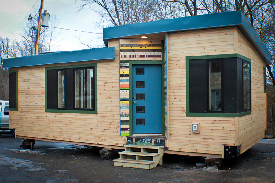 Impressive Tiny House Builders Exterior with Wooden Wall and Blue Accents for Roof Line and Entrance Door