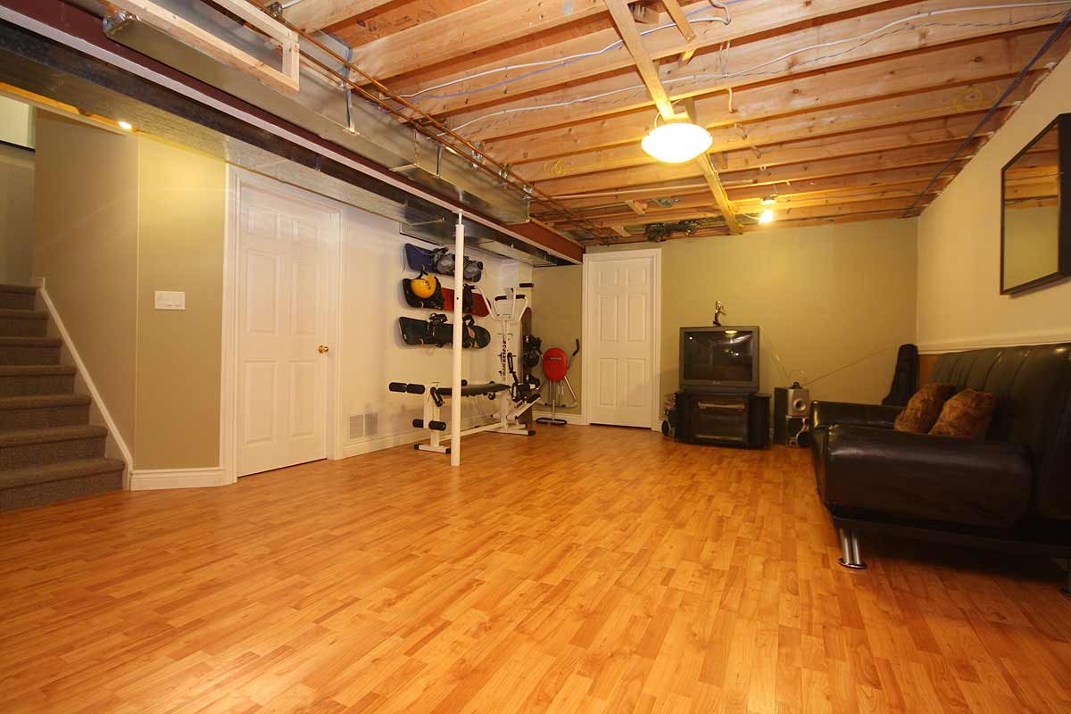 Beau Industrial Basement Interior With Wooden Flooring And Brown Leather Sofa