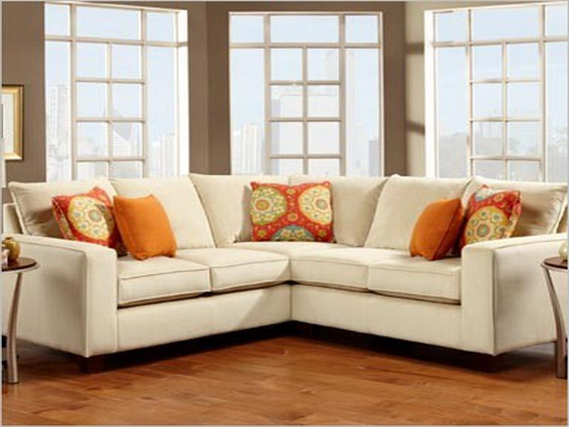 Laminate Teak Flooring inside Comfy Sitting Area with White Small Sectional Sofa and Round Side Tables