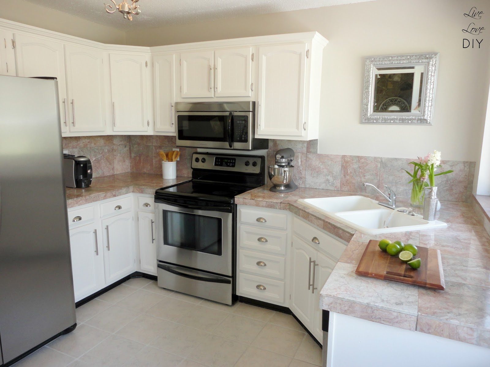 Marble Top and White Painted Kitchen Cabinets Placed inside Small Kitchen with Tile Flooring