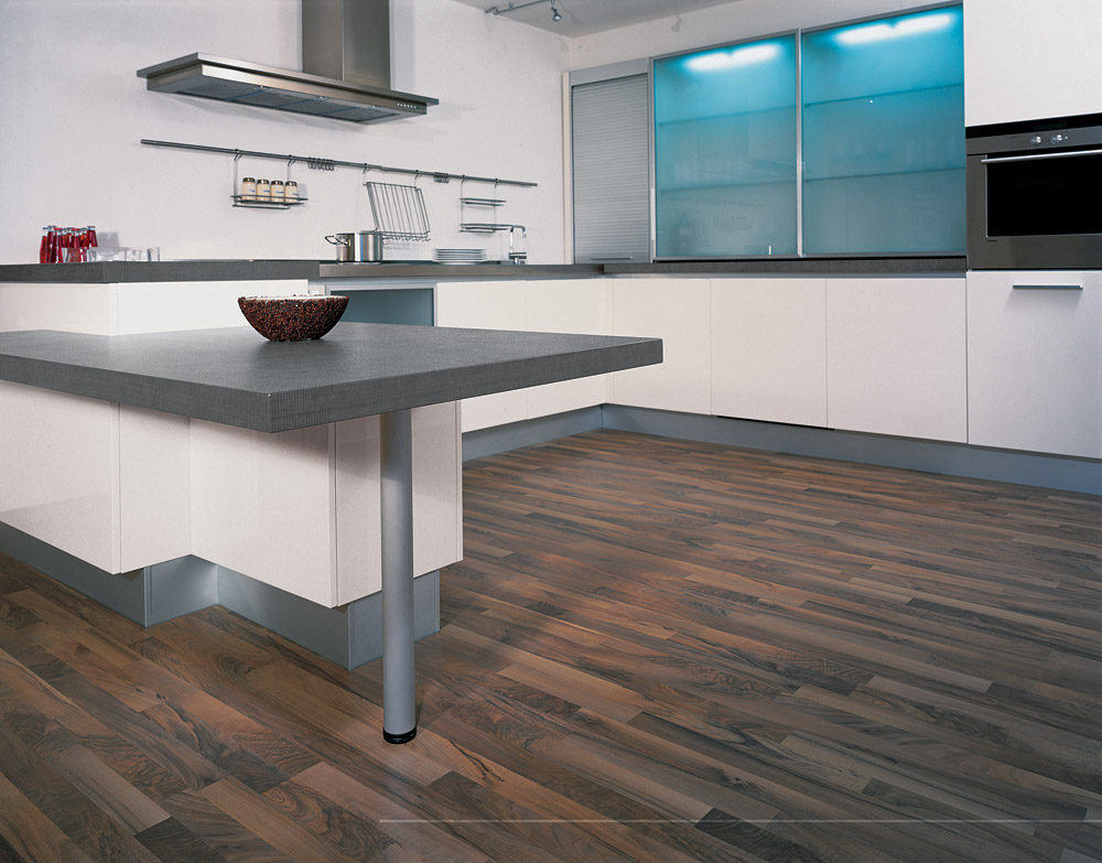 Natural Wood Laminate Flooring Installed under White Cabinets and Grey Concrete Countertop in Modern Kitchen