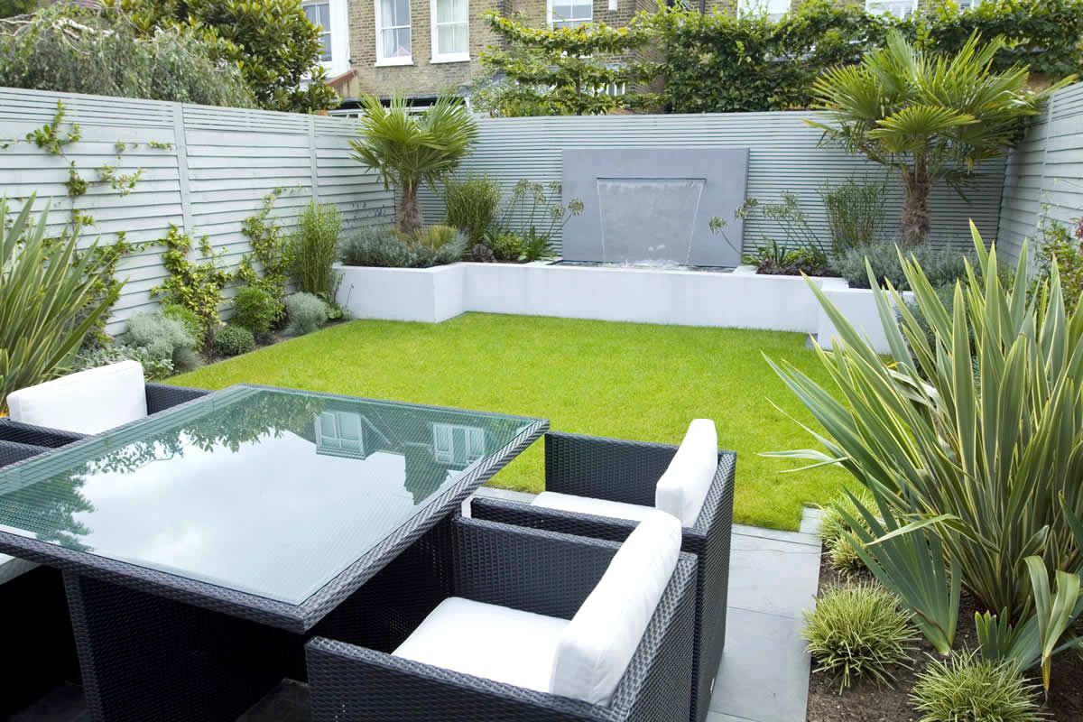 Neat Lawn Surrounded with Flower Bed and Green Plantation for Refreshing Small Patio
