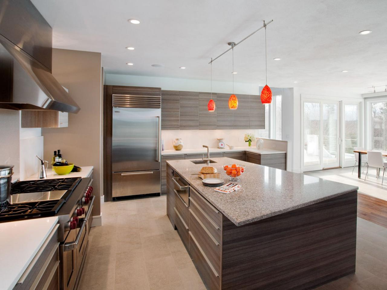 Orange Ceiling Lamps above Stylish Wooden Island in Open Kitchen with Modern Kitchen Cabinets