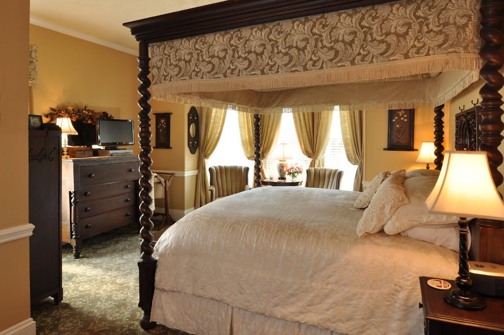 Place Wide Dark Canopy Bed Frame and White Bedding in Traditional Bedroom with Wooden Dresser