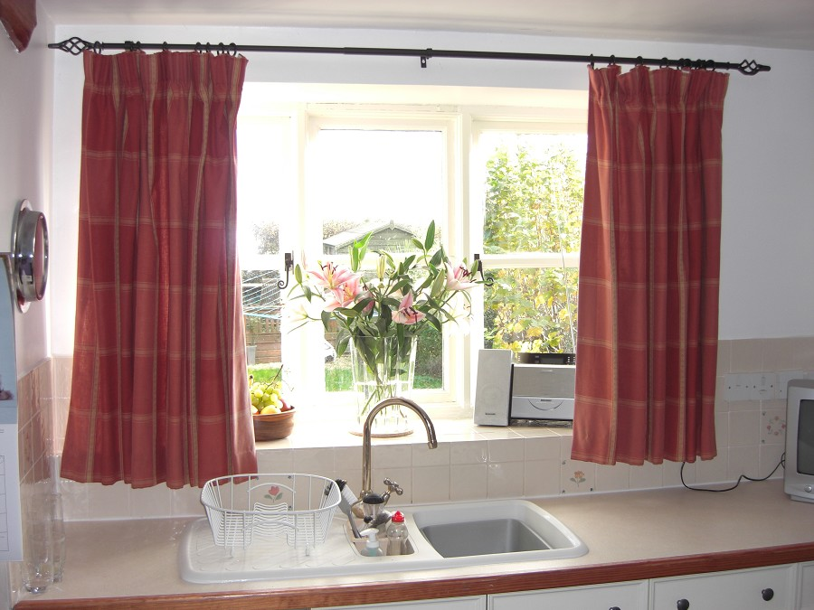 Protective Red Patterned Curtains to Cover Kitchen Windows with Flowers on Sill