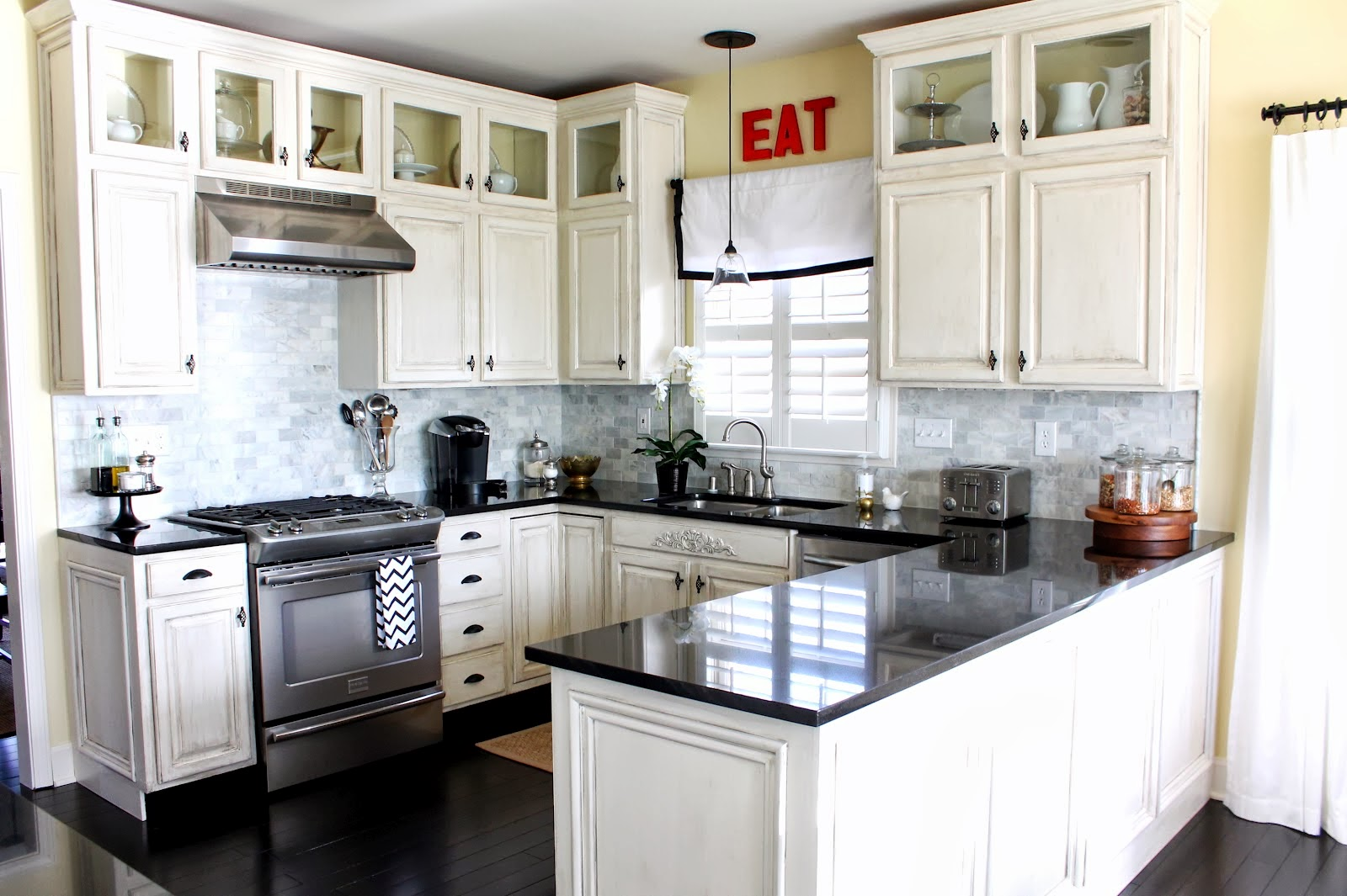 Reflective Granite Countertop and White Kitchen Cabinets in Small Open Kitchen with Classic Sink