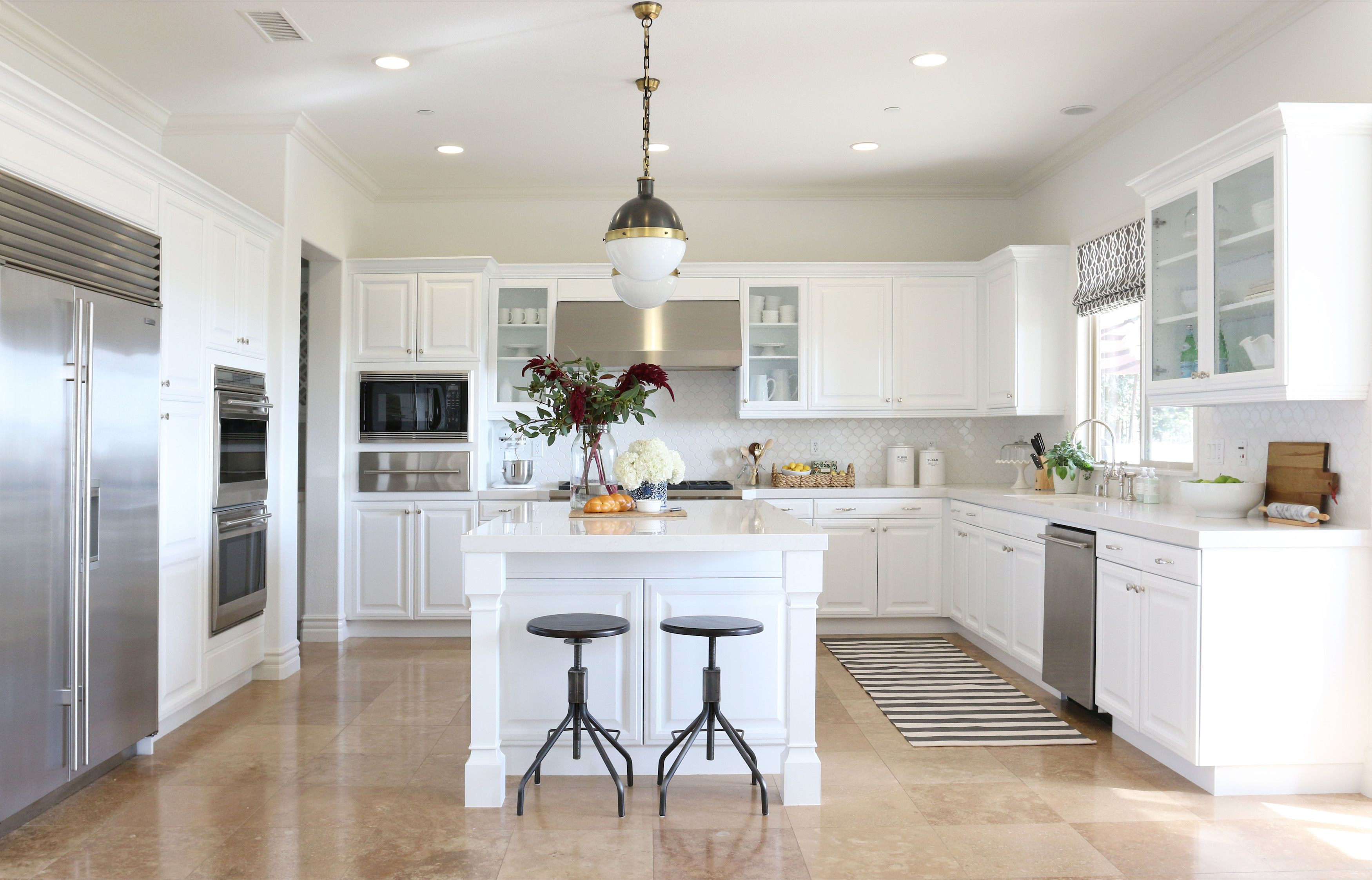 Round Metal Stools and Wide Island inside White Themed Kitchen with Clean White Kitchen Cabinets