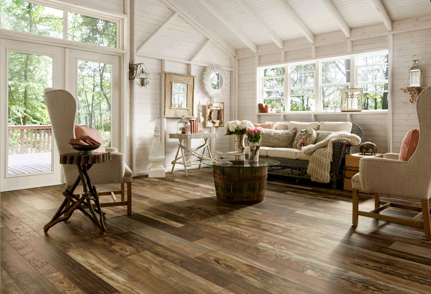 Rustic Living Room using Wood Laminate Flooring under Wicker Sofa and Cozy Wingchairs near Round Table