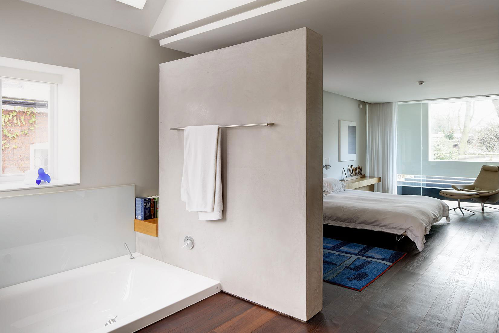 Simple Concrete Room Divider with Stainless Towel Rack Separating Bathroom from Bedroom