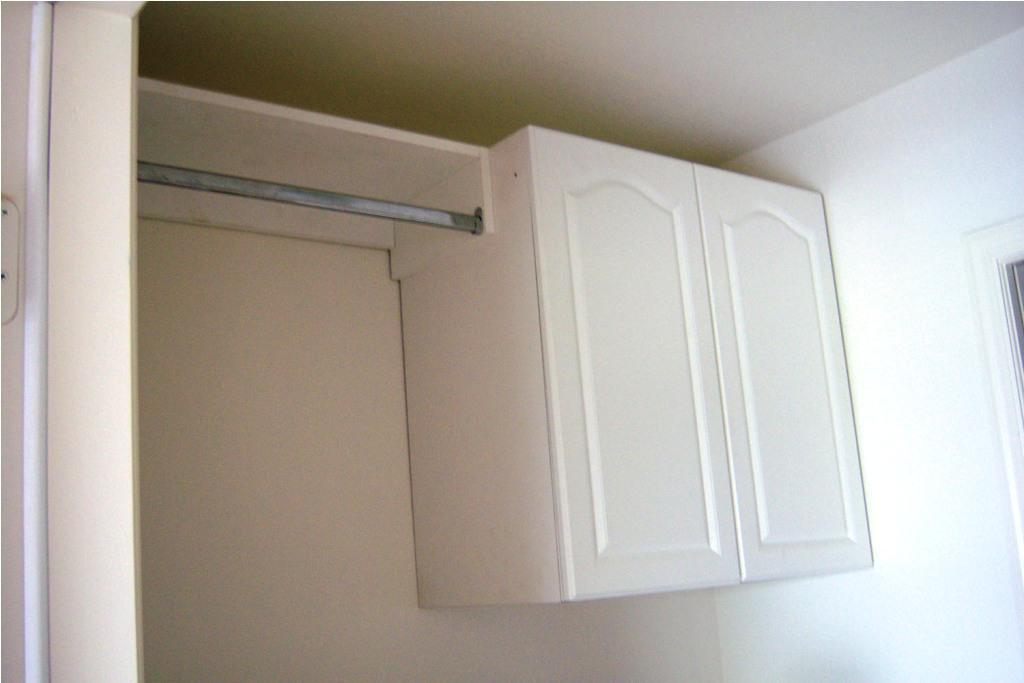 Simple Laundry Room Cabinets in White Color beside Clothes Hanger inside Small Room