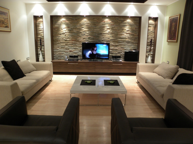 Stunning Lighting for Modern Living Room with Stone Wall and Wooden Cabinets facing Marble Top Coffee Table