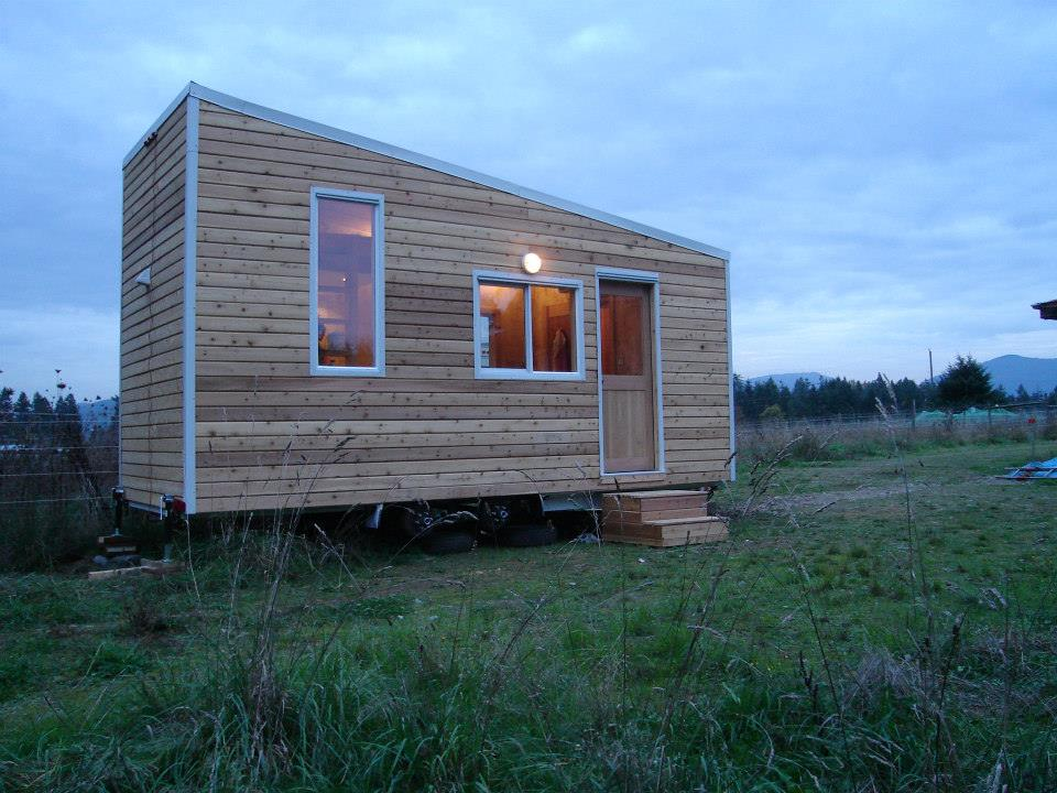Trapezoidal Tiny House Architecture with Wooden Exterior and Decorative Trims