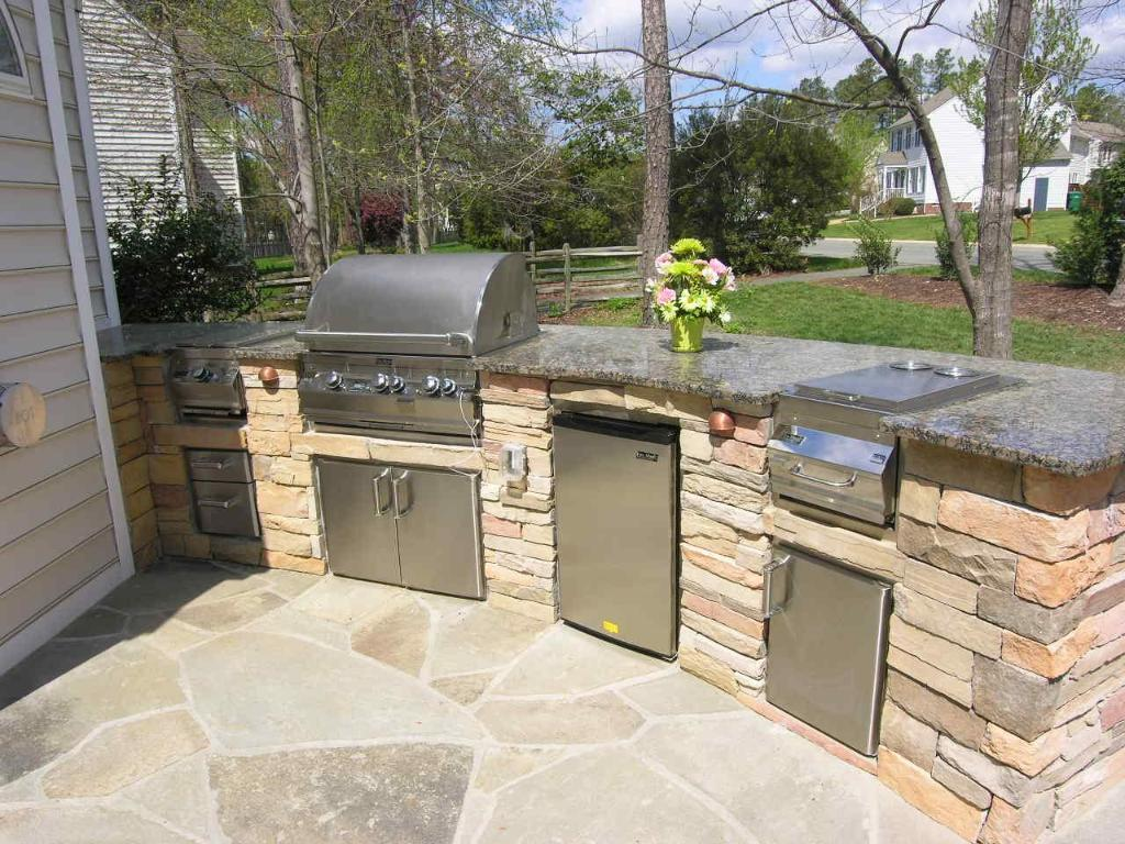 Unique Curvy Shaped Outdoor Kitchen with Stone Brick Island and Granite Top