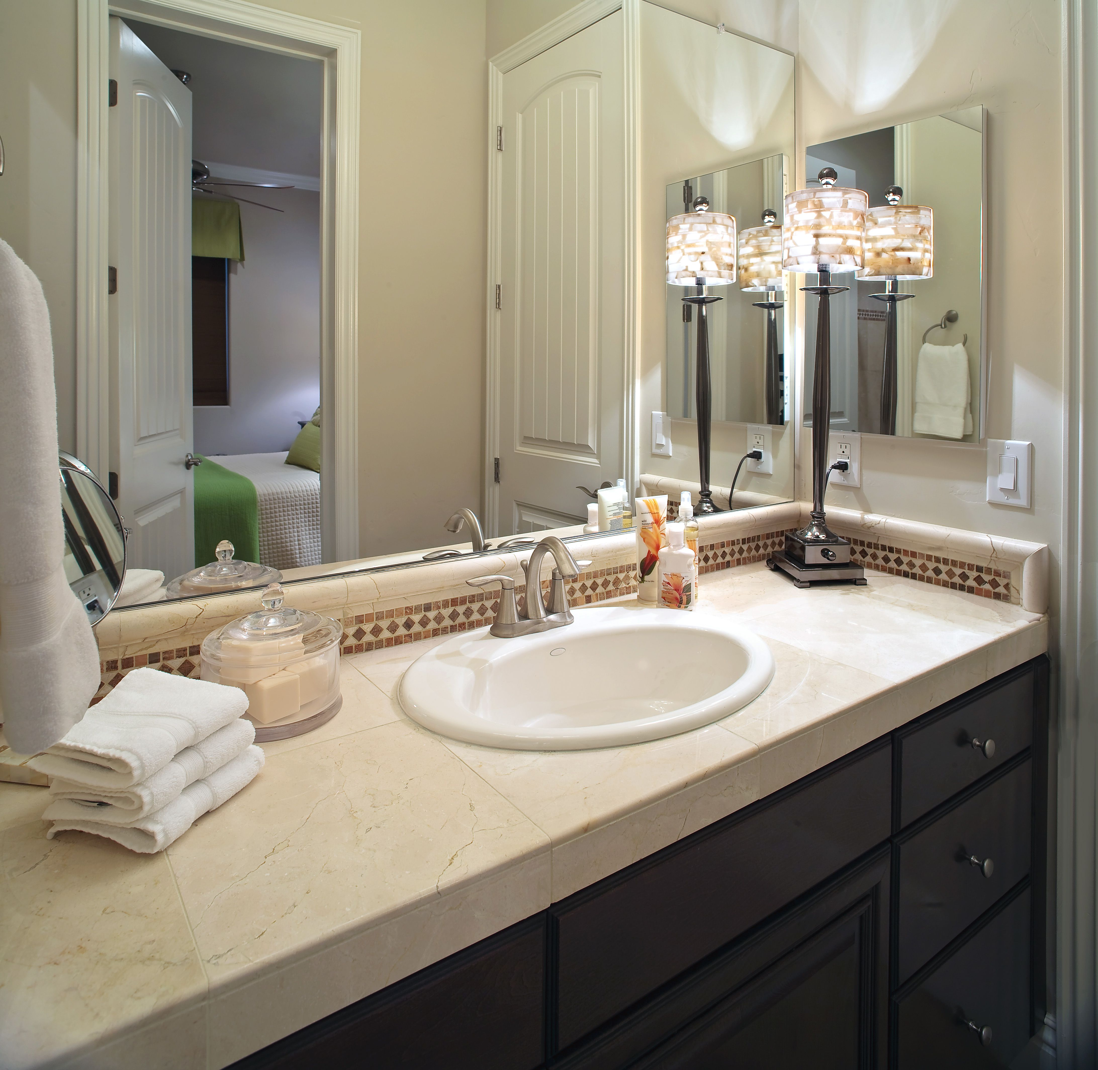 Unique Decorative Lighting Displayed on Black Vanity with Single Sink and Double Mirrors