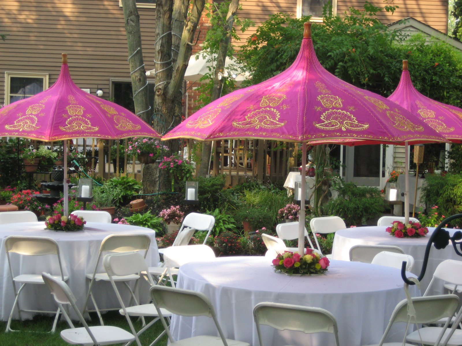Unique Parasols with Rounded Table Surrounded by Chairs as a Simple Party Decoration Idea