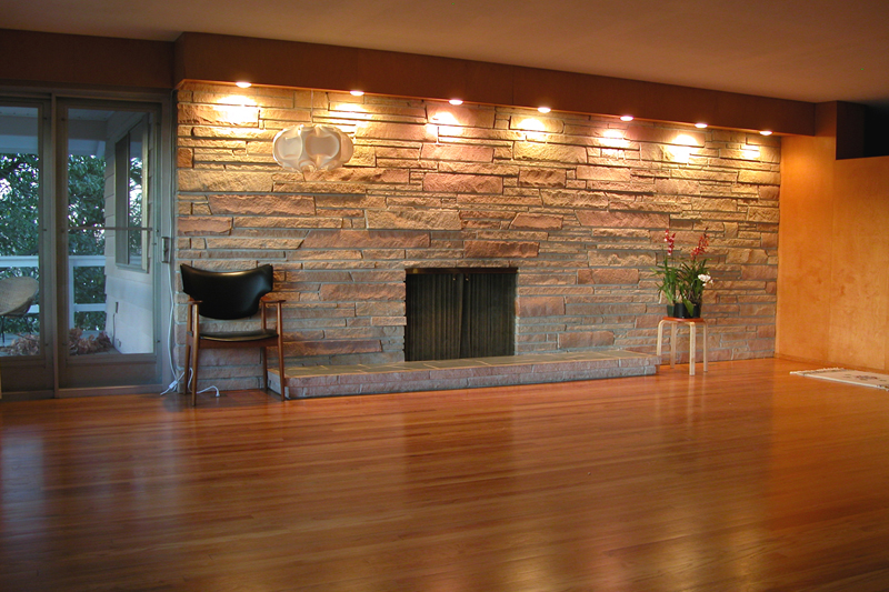 Use Brown Wood Laminate Flooring inside Spacious Room with Natural Grey Stone Wall and Bright Lamps