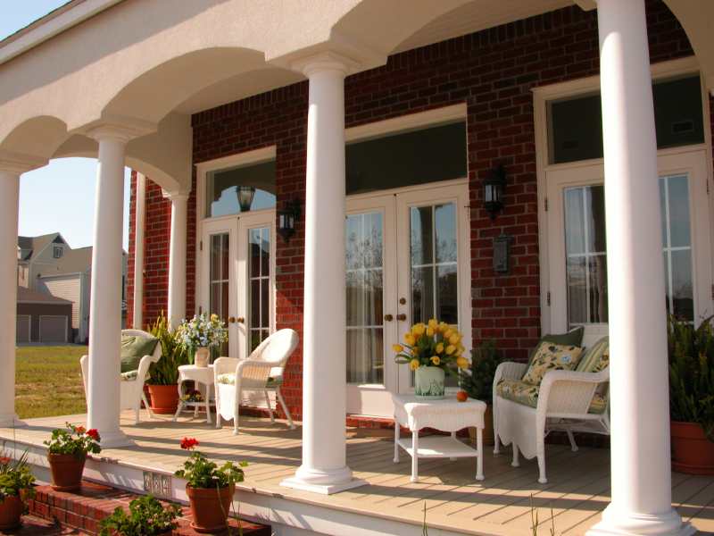 Use White Wicker Chairs and Table for Comfortable Front Porch Ideas with Wooden Flooring and Brick Wall