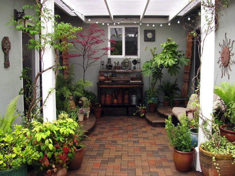 well arranged vases and greens while also displaying decorative elements in small patio - Outdoor Small Patio Ideas