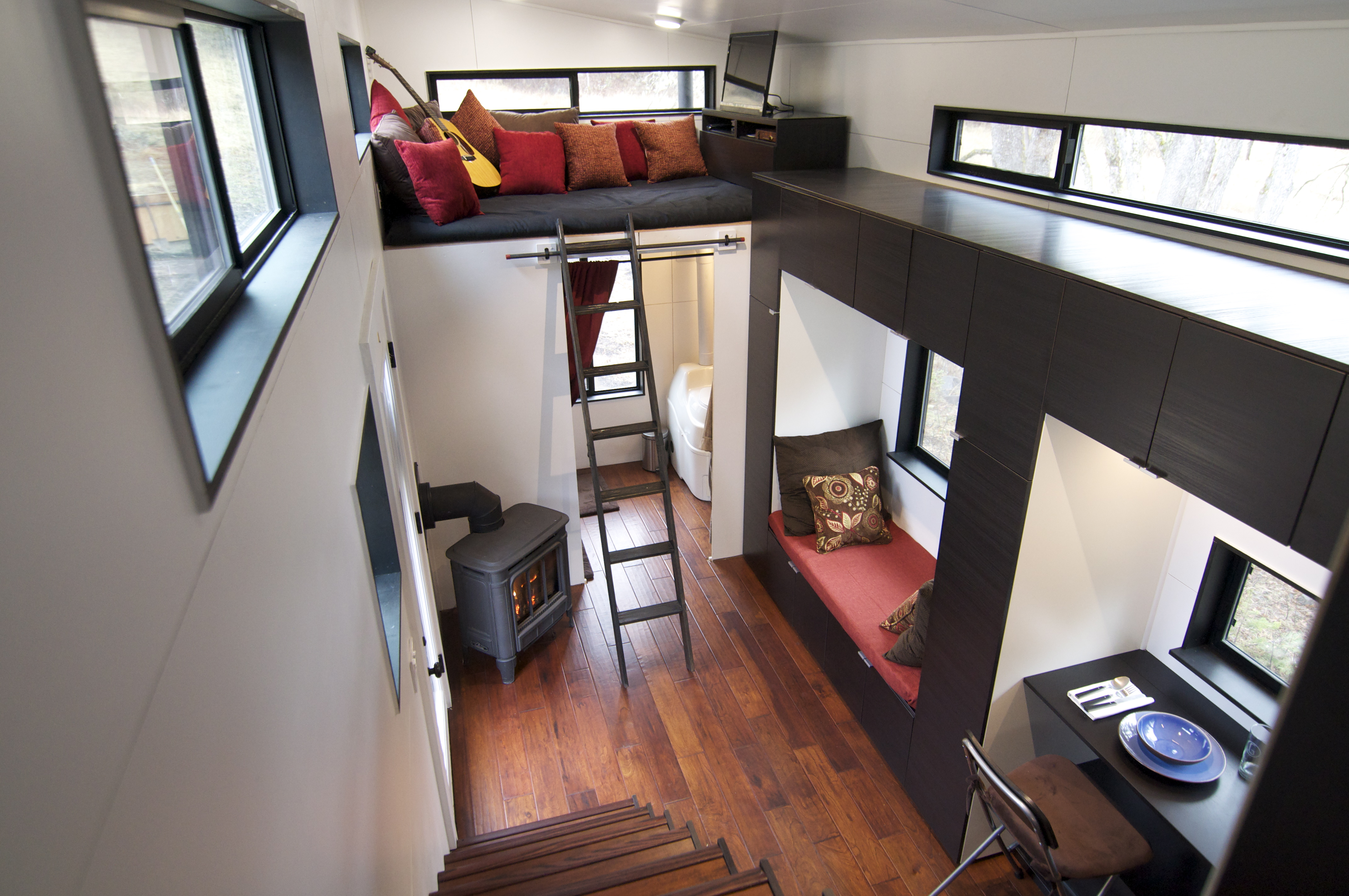 Well Organized Tiny House Interior with Multi Purpose Seating Units and Double Height Ceiling