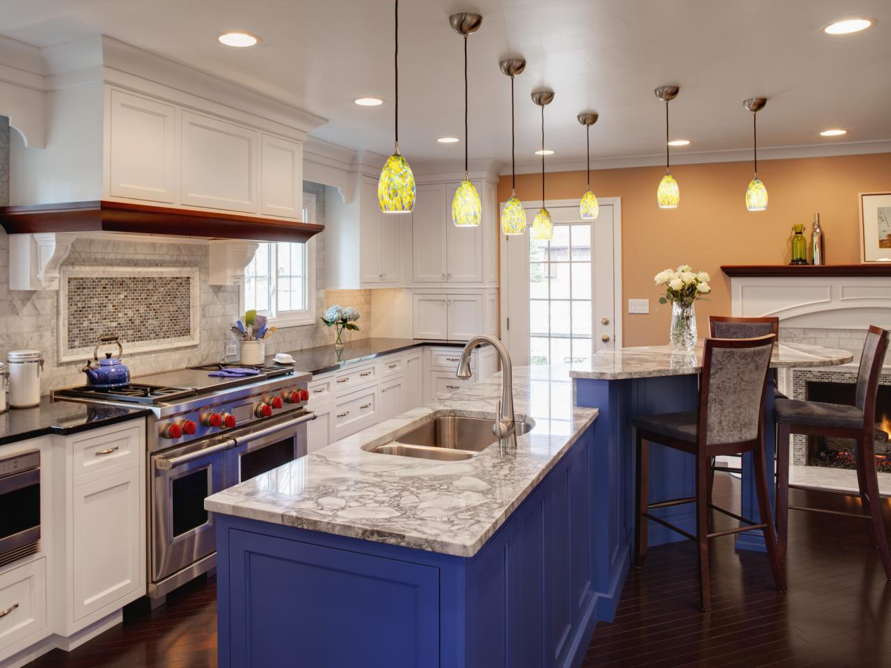 White Painted Kitchen Cabinets and Blue Island inside Wide Kitchen with  Wooden Stools and Grey Backsplash