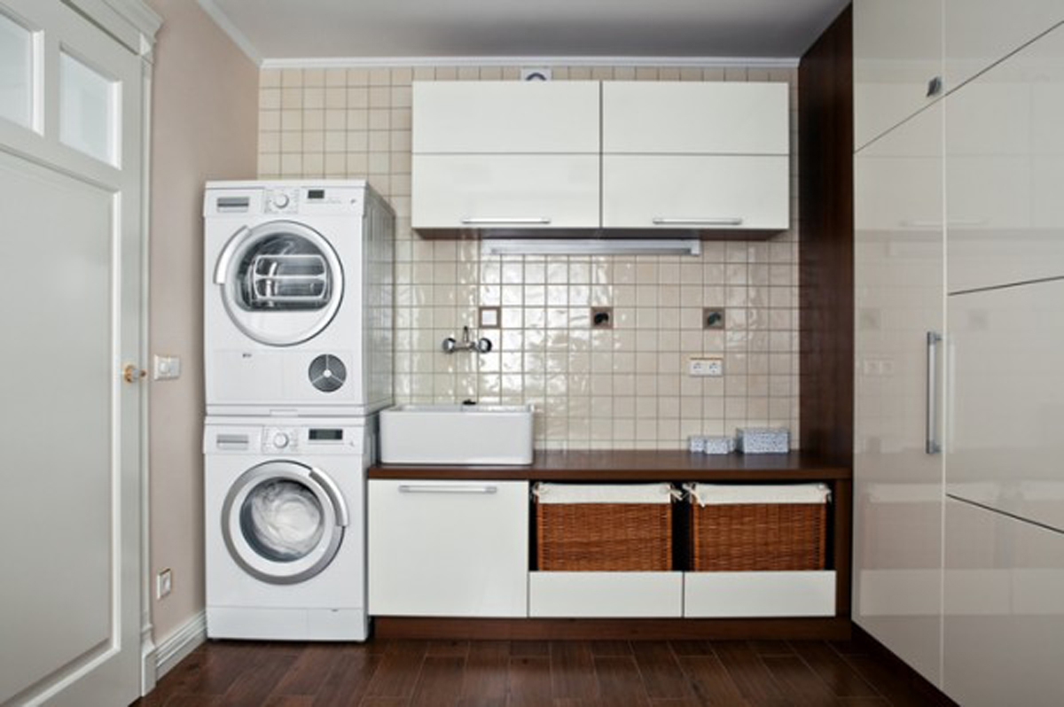 White Stacked Washing Machines and Wide Wicker Basket Placed near White Laundry Room Cabinets