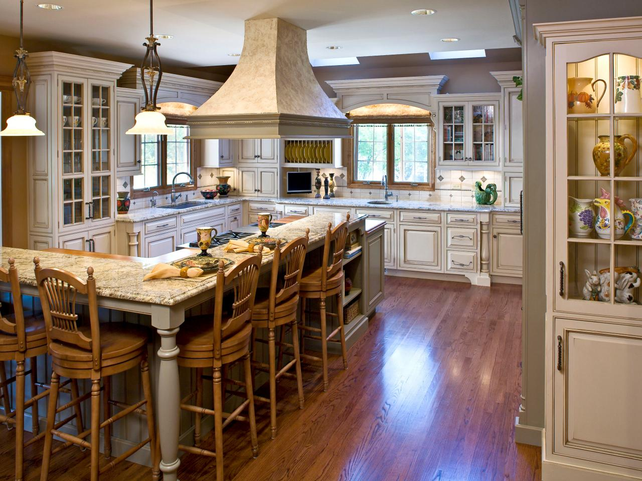 Wide Range Hood above Classic Kitchen Island Table and Old Fashioned Stools inside Elegant Kitchen