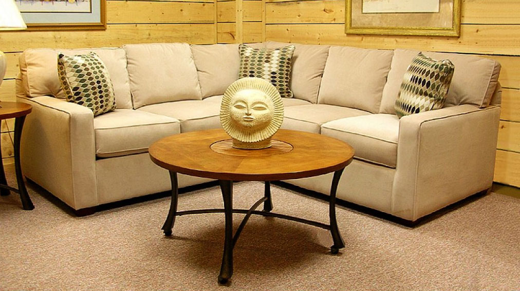 Wooden Wall and Small Sectional Sofa facing Round Oak Table on Brown Granite Tile Flooring
