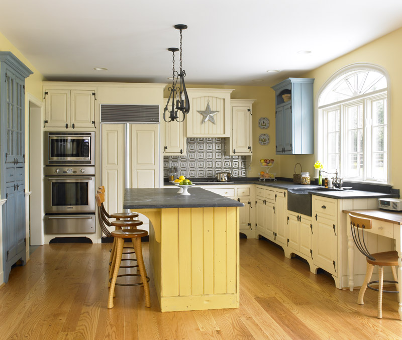 Add Kitchen Islands with Round Oak Seating for Old Fashioned Kitchen using White Cabinets on Wooden Flooring