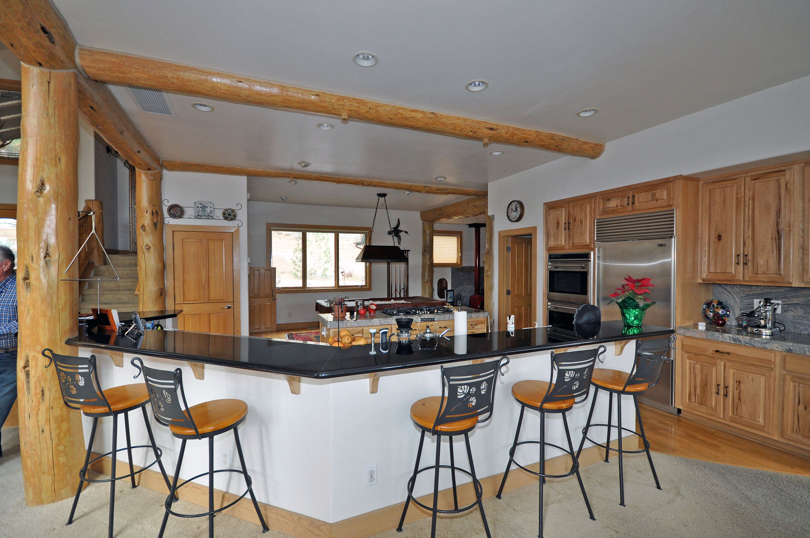 Appealing White Kitchen Island with Stools and Dark Countertop Used in Rustic Kitchen using Log Pillars