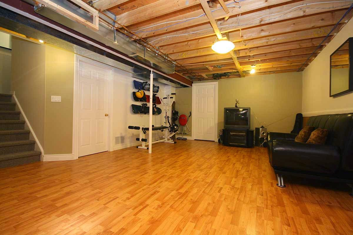 Bright Ceiling Lamp and Wooden Beams Used for Simple Basement Ceiling Ideas above Black Leather Sofa