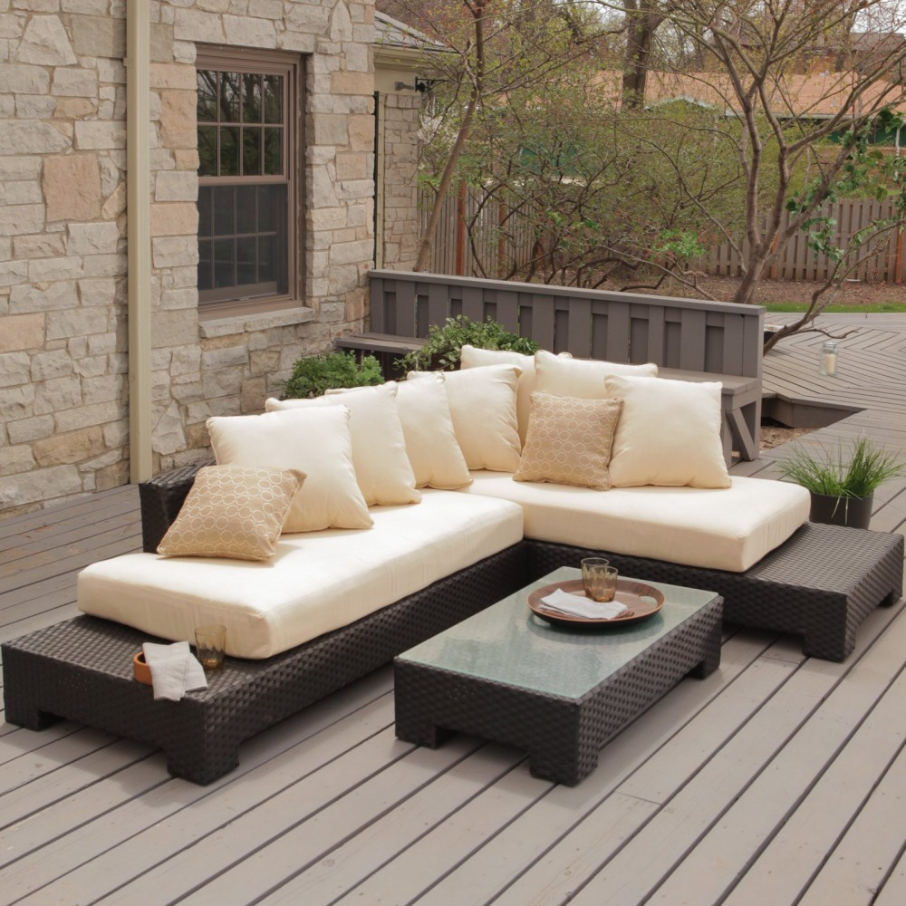 Choose Low Wicker Table and Sectional Sofa for Modern Patio Furniture on Wide Oak Deck near Stone Wall