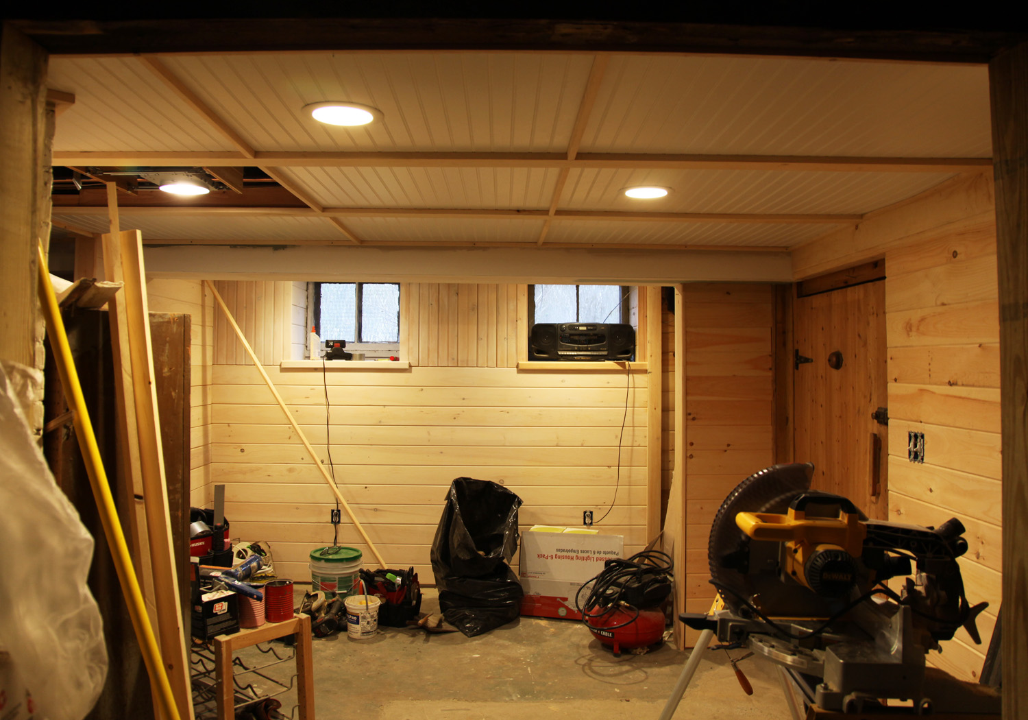 Choose Minimalist Basement Ceiling Ideas with Bright Planted Lamps and Wood Panels above Concrete Flooring