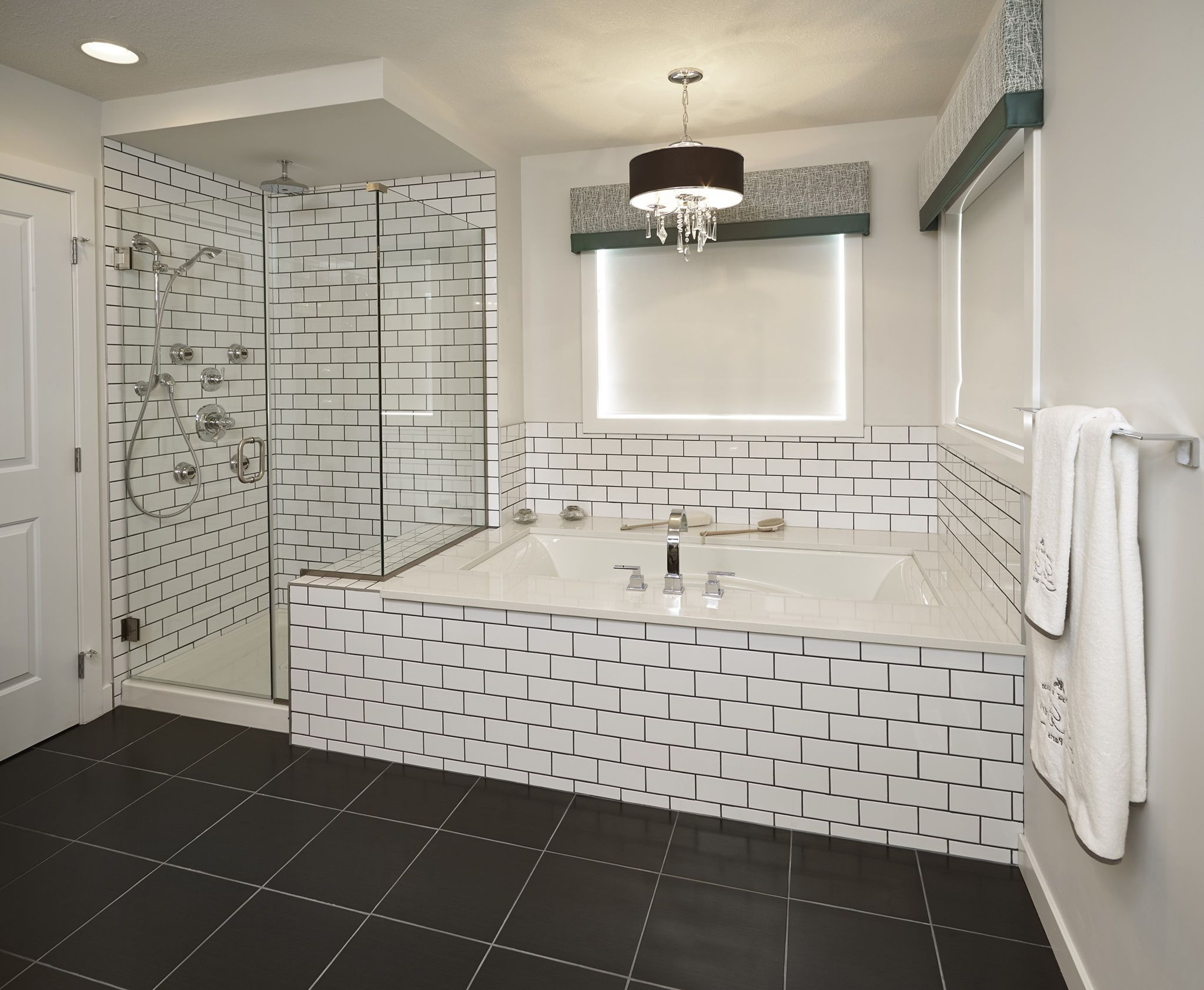 Classic Black Drum Shaded Chandelier above White Bathtub and White Subway Tile Bathroom Wall