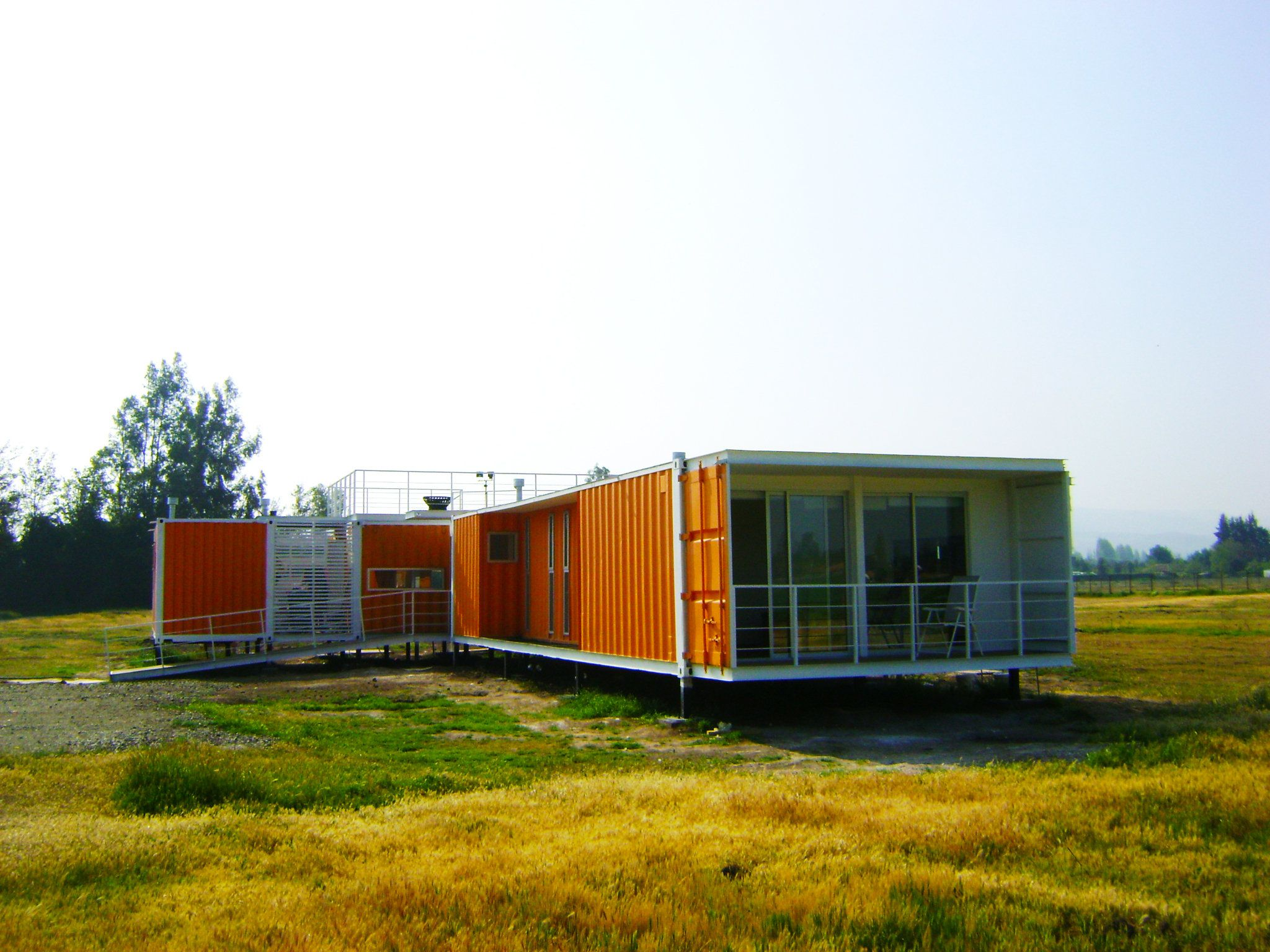 Comfy Balcony for Cargo Container Homes with Orange Wall and Flat Roof facing Green Grass Area