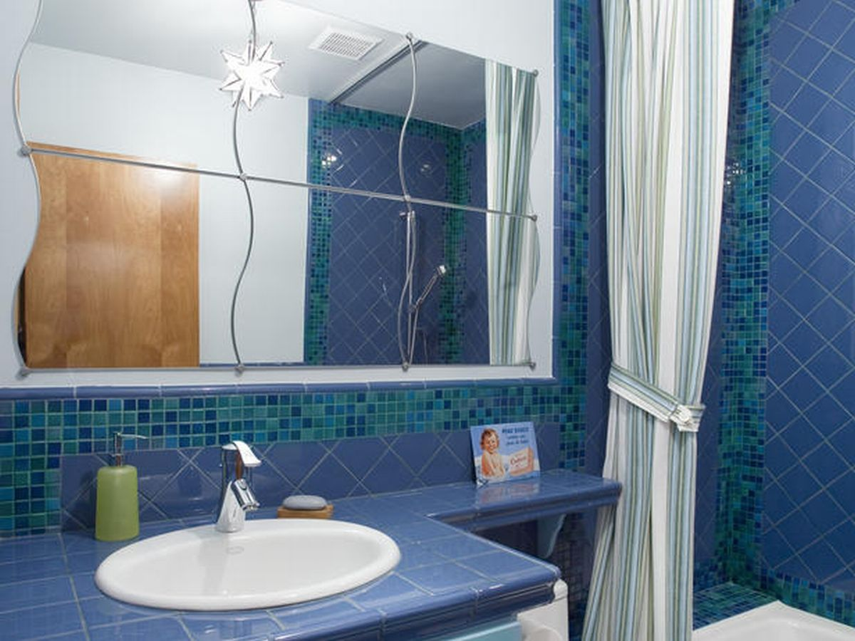 Complete Blue Bathroom Paint Ideas with Unique Wavy Wall Mirrors above White Sink and Tile Vanity Top