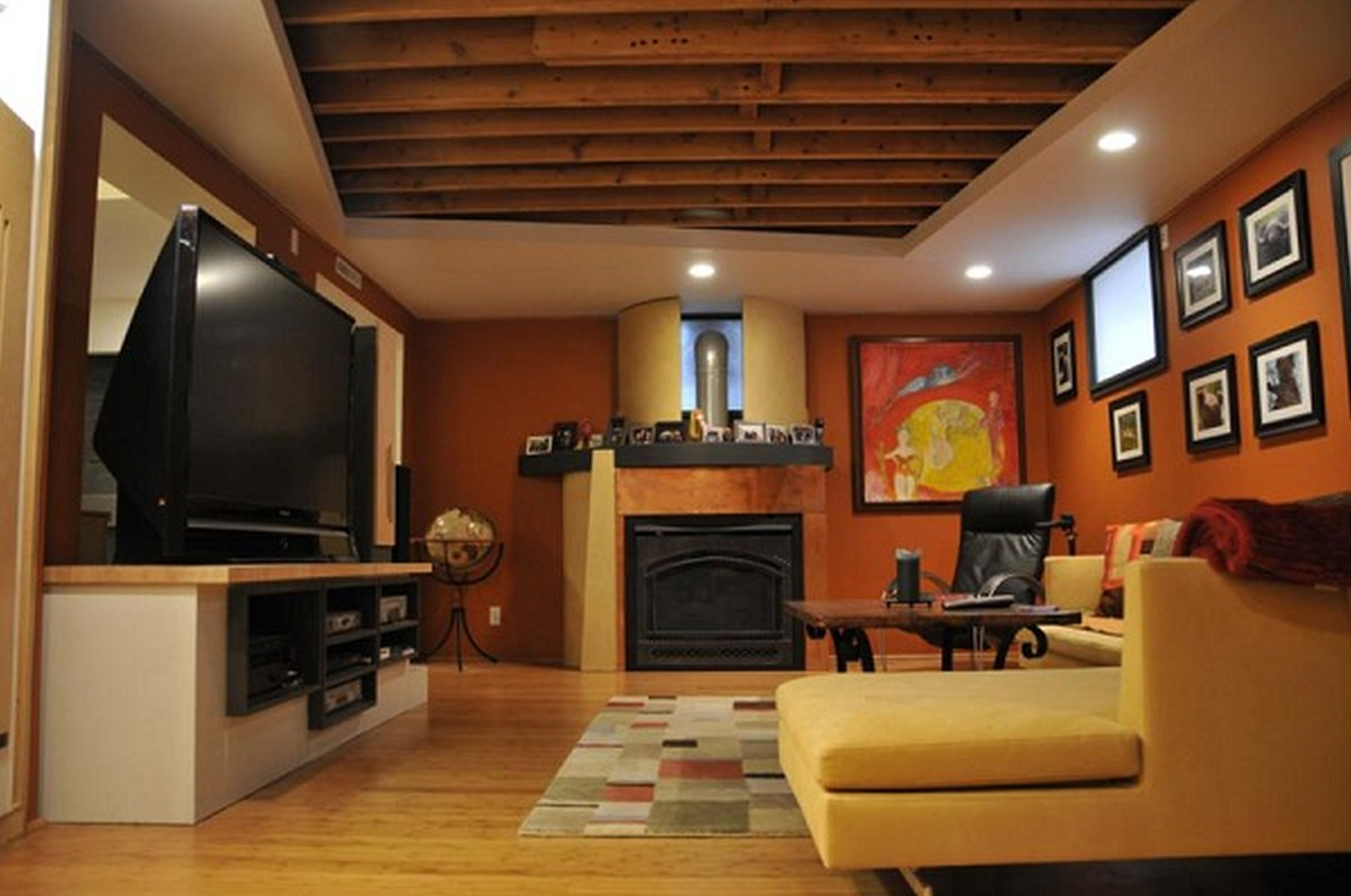 Complete Cozy Media Room with Cream Sectional Sofa and Black Fireplace under Wooden Basement Ceiling Ideas