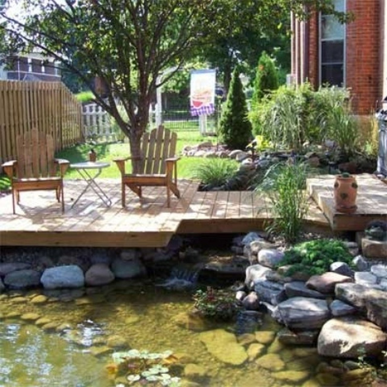 Complete Interesting Flower Garden Ideas with Wooden Deck and Pond Like Pool near Oak Chairs and Stones